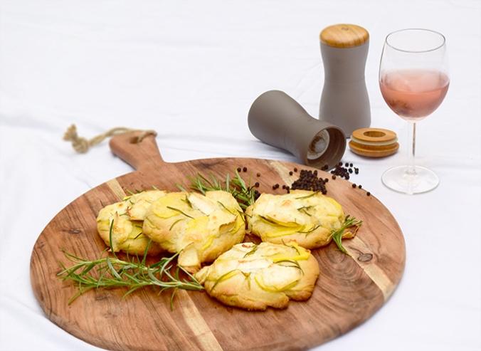 Minifocaccia auf Holzbrett Weinglas Pfeffer