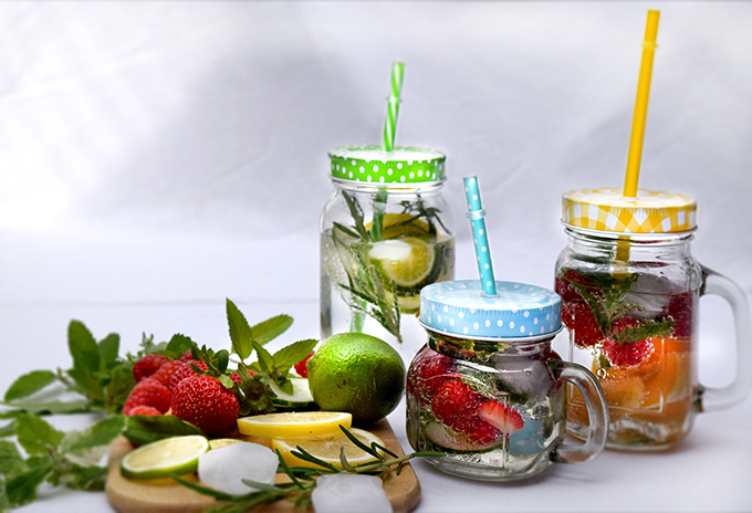 Gläser mit Früchten Wasser Zitronen Erdbeeren Kräuter Dekoration
